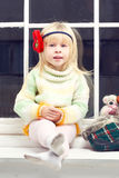 Little girl in knitted sweater on the window Royalty Free Stock Photography
