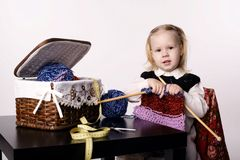 Little girl knitting scarf Stock Photo