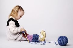Little girl knitting scarf Royalty Free Stock Photo