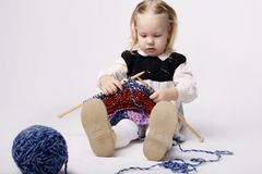 Little girl knitting scarf Royalty Free Stock Image