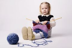 Little girl knitting scarf Royalty Free Stock Photos