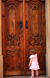 Little girl knocking at the door. Little girl knocking at a big door Royalty Free Stock Image