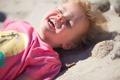 Baby girl beach. Little girl l at the beach having fun,lying in the sand and laughing out loud royalty free stock photos