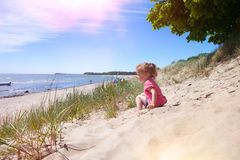Baby girl beach. Little girl l at the beach having fun, sitting in the dunes and looking to the sea, baltic sea, isle of ruegen stock photography