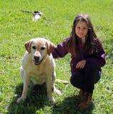 Little girl with labrador retriever dog. Cute little girl with labrador retriever dog on the grass Stock Photos
