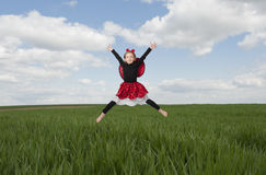 Little girl in lady bug costume jumping in the fileds Stock Image