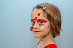 Little girl with ladybug face paint Stock Images
