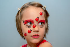 Little girl with ladybug face paint Stock Photo