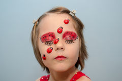Little girl with ladybug face paint Stock Photos
