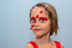 Little girl with ladybug face paint Stock Photography