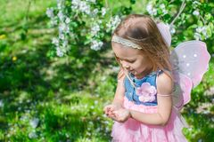 Little girl with a ladybug in the hands at. Little girl with a ladybug in the hands in the apple orchard Royalty Free Stock Image