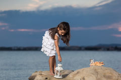 Little girl with lantern on the rock and starfish Royalty Free Stock Photos