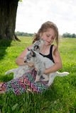 Little girl with a lap full of puppies Royalty Free Stock Image