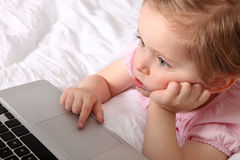 Little girl with laptop. On the bed royalty free stock image