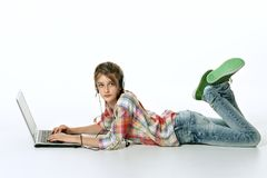 Little girl and laptop. One little girl lying at the floor and using laptop stock photography