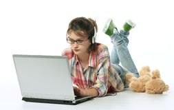 Little girl and laptop. One little girl lying at the floor and using laptop royalty free stock images