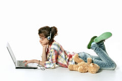 Little girl and laptop. One little girl lying at the floor and using laptop royalty free stock photography