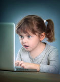 Little girl with laptop. Playing computer games Royalty Free Stock Photo