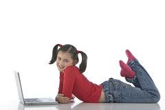 Little girl with laptop. Adorable caucasian little girl lying with laptop royalty free stock image