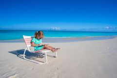 Little girl with laptop on beach during summer Stock Image