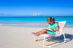 Little girl with laptop on beach during summer Royalty Free Stock Photo