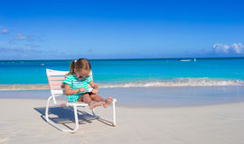 Little girl with laptop on beach during summer Stock Images