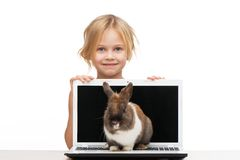 Little girl with laptop and bunny on it Stock Photos