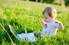 Little girl at the laptop. Clever little girl sitting on the green grass with laptop royalty free stock image