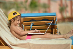 Little girl with laptop. Cute little girl with laptop on resort on deck chair Stock Photography
