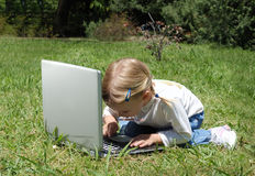 The little girl with laptop on a glade Stock Image
