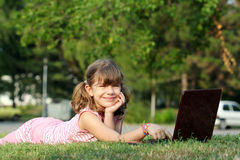 Little girl with laptop lying on grass Stock Images