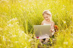 Little girl with laptop on nature Royalty Free Stock Images