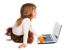 Little girl with laptop and orange Stock Images