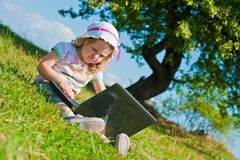 Little girl with laptop outside on grass Stock Photos