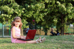 Little girl with laptop in park Royalty Free Stock Photos