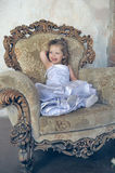 Little girl  in a large antique chair Royalty Free Stock Images