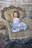 Little girl  in a large antique chair Stock Photo