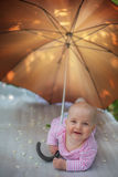 Little girl with a large color umbrella. Child hiding from the sunlight under an umbrella Stock Photo