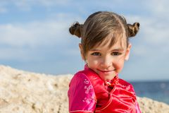 A little girl on with large swivel-eyed eyes is put and brushed japanesque smiles on a background a rock sea. royalty free stock images