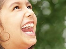 Little girl laughing. A close up view of a little girl with her mouth open as she laughs while looking upwards Royalty Free Stock Photography