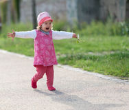 Little girl laughing with arms outstretched Stock Images
