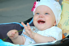 Little girl laughing in carriage. Pretty little girl with blue eyes (baby) laughing in carriage royalty free stock photos