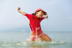 Little girl laughing and crying in the spray of waves at sea Royalty Free Stock Photo