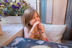 Little girl laughing with fork in restaurant Royalty Free Stock Photos