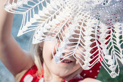 Little girl is laughing and hiding behind the crochet hat Royalty Free Stock Images