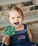 Little girl laughing holding a lollipop Royalty Free Stock Photo