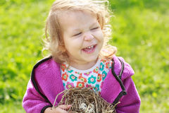 Little girl laughing during holding nest with eggs Stock Photos