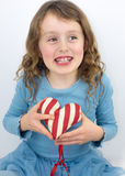 Little girl laughing and holding a valentine heart Royalty Free Stock Images