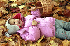 Little girl laughing while lying on the ground Royalty Free Stock Photography