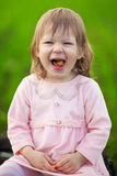 Little girl is laughing in the middle of the field. Stock Photos